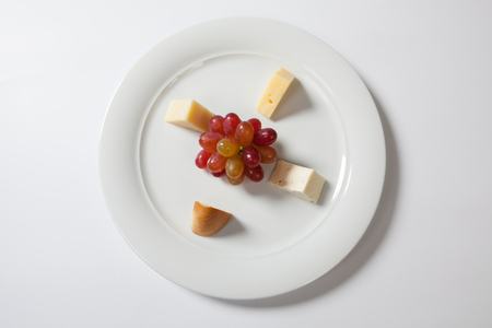 galettes: Assorted cheeses and grape on a white plate. Stock Photo