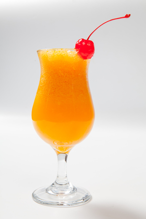 orange cocktail decorated with cherry on white background. Stock Photo