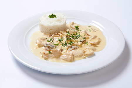 stewed chicken with white rice and mashroom sauce on the white plate Stock Photo