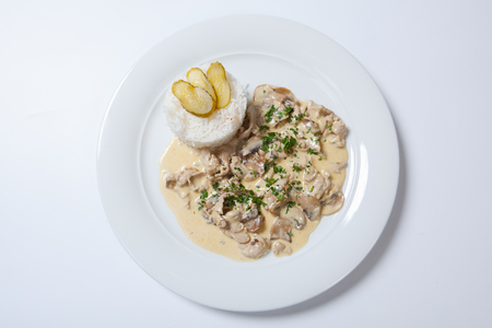 polish chicken: stewed chicken with white rice and mashroom sauce on the white plate Stock Photo