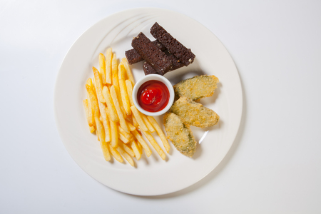 oily: Fresh beer snacks assortment on a white plate. French fries, croutons and zucchini.