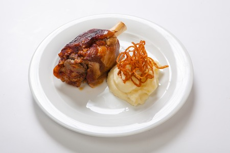 Bavarian roasted knuckle of pork and mashed potatoes on bright background.