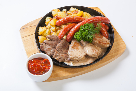 green bean: grilled sausages with potatoes, and roasted meat on a grill pan. Stock Photo