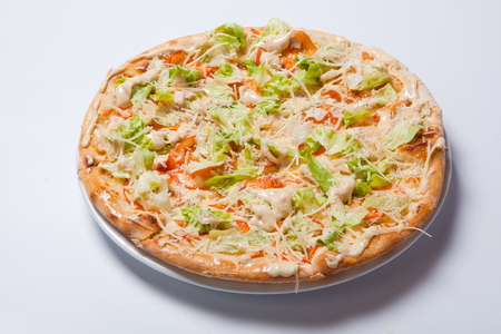 Italian delicious pizza with tomato, lettuce and cheese.White background