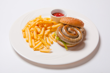 Tasty burger with fried potatoes and sausage, on white plate.