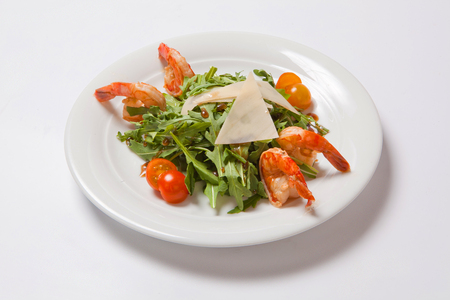 A delicious salad with arugula, cherry tomatoes and shrimps.