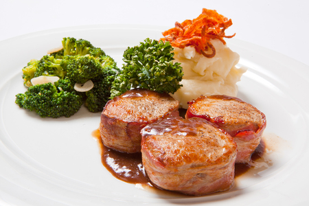 Pork medallions wrapped in bacon, with potatoes and broccoli.