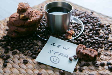 textured wall: coffee cup and coffee beans on wooden table with cookies and notepad with message on the sticker.