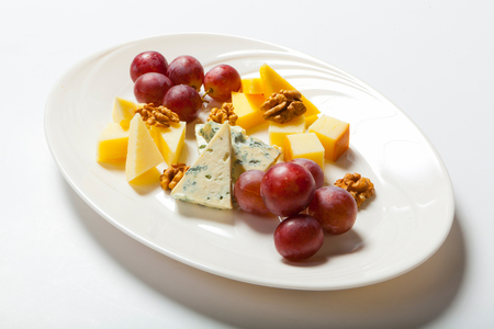 roquefort: cheese and nuts, and grapes on the white plate.