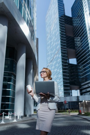 Young beautiful business woman with cup of coffee and laptop in her hands standing among the downtown Banco de Imagens - 112460976