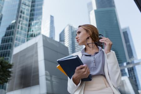 Junge Frau mit Ordnern und Dokumenten in den Händen, die zwischen den Wolkenkratzern des modernen Geschäftszentrums steht