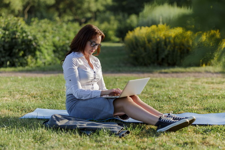Beautiful big girl lying on the green grass in park with her laptop and working. Student girl looking at the computer screen. Stockfoto