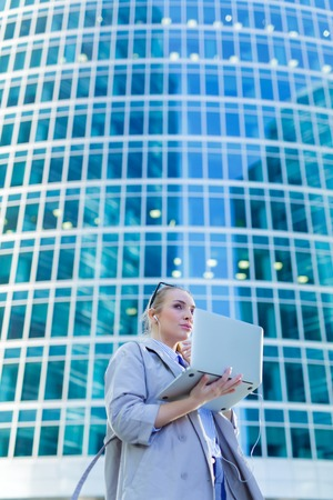 Business woman standing with a laptop in the city center 스톡 콘텐츠