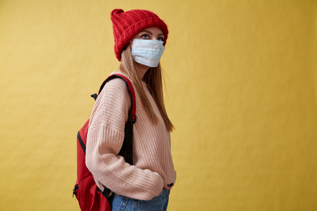 Ill girl in red hat and the medical mask on the yellow background
