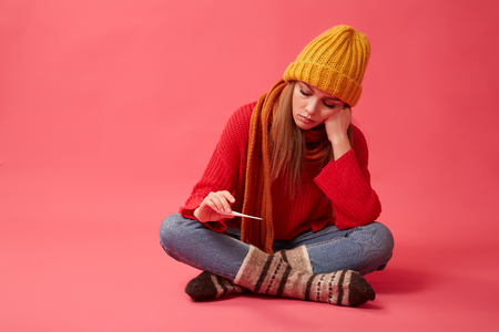 A diseased woman in a yellow hat holds a medical thermometer in her hands. Image on the pink background Stock Photo