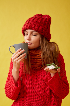 Sick woman holding pills and a cup in her hands. Image on yellow background.