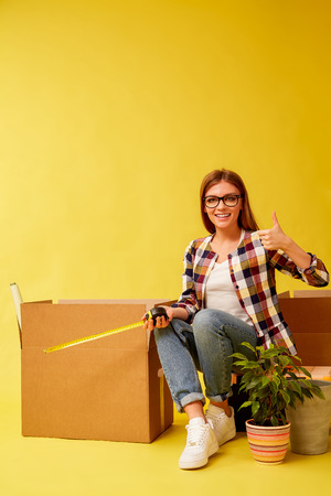 Young girl holding a flower, sitting on a tool box, between boxes for moving. People moving new place and repair concept. Yellow background.
