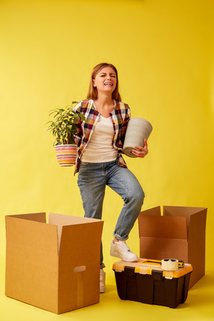 Student stands with a flower and a pot in her hands between cardboard boxes for moving. People moving new place and repair concept. Yellow background.