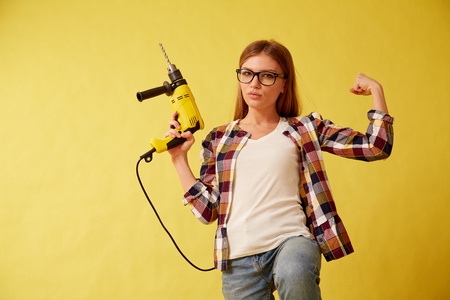The girl skillfully holds a drill, standing between the boxes. Yellow background