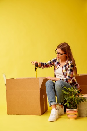 Young girl holding a measuring tape, sitting on a tool box, between boxes for moving. Yellow background. Stockfoto