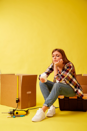 Move. Girl drinking coffee sitting on a tool box. Yellow background