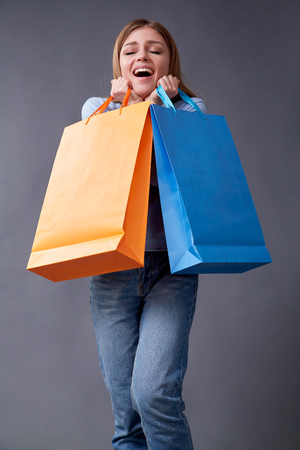 Emotional woman with colored packages standing on a gray background after shopping. Studio 免版税图像