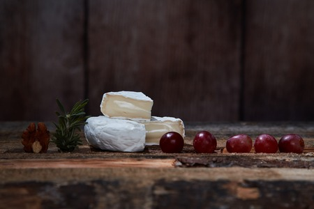 Soft gourmet cheese with grapes and rosemary on wooden table Foto de archivo