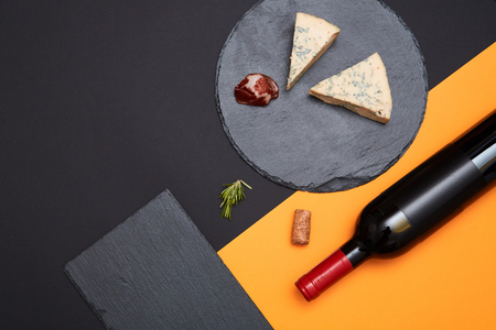 Layout of blue cheese with prosciutto slices on black slate board with bottle of wine on colorful background