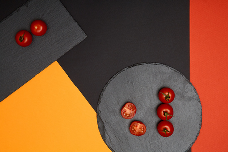 Ripe cherry tomatoes composed on black slate boards on colorful background