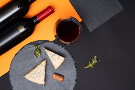 Composition of blue cheese with prosciutto slices on black slate board with bottle of wine on colorful background Stock Photo
