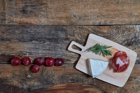 Layout of grape berries and wooden board with cheese and prosciutto slices on wood planks