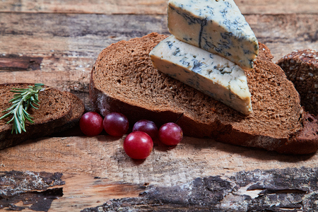 Cereal bread slices with aromatic blue cheese and grape berries on wooden planks