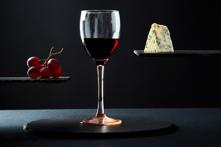 Composition of red wine in glass beside blue cheese and grape on black background. 스톡 콘텐츠