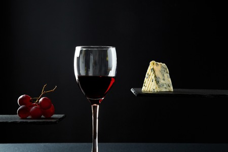 Composition of red wine in glass beside blue cheese and grape on black background 스톡 콘텐츠