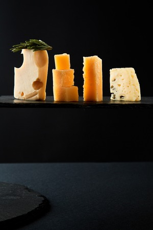 Different sorts of cheese on the black background. Studio Image. 스톡 콘텐츠