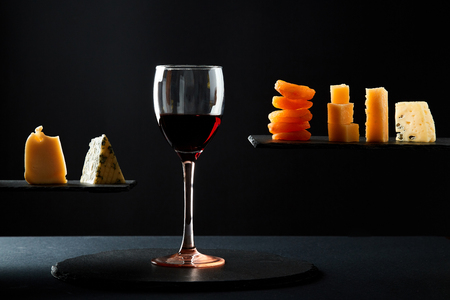Pieces of cheese and dried fruit beside glass of red sweet wine on black background. 스톡 콘텐츠