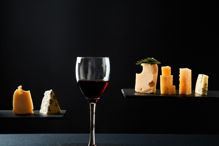Fragrant red wine in glass beside sliced fresh cheese of different sorts.