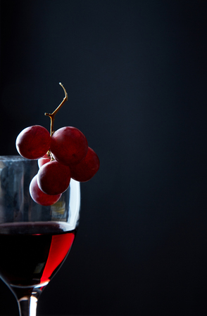 Glass of delicious red wine garnished with bunch of grapes on black background.