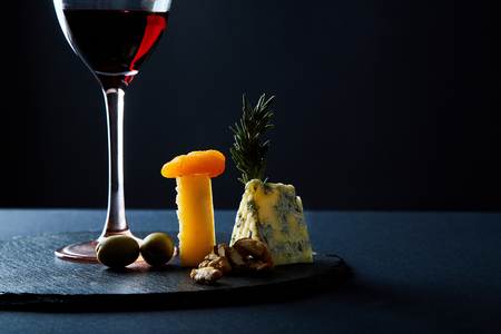 Composition of traditional appetizer for red wine on slate board.