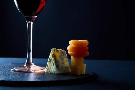Glass of delicious red wine among traditional appetizer for red wine on slate board. Stock Photo