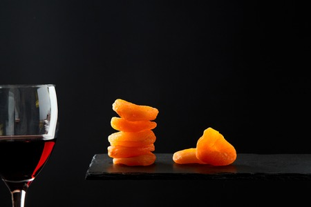 Dried fruit or dried apricot beside glass of red sweet wine on black background.
