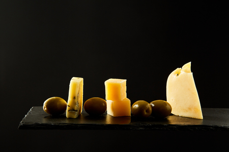 Savory green olives and pieces of fresh hard cheese placed on black background.
