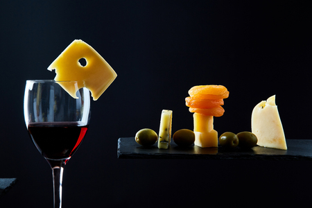 Glass of tasty red wine among assorted traditional appetizers on black background.
