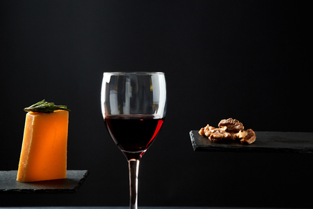 Red wine in crystal glass beside pieces of cheese and walnut on black background