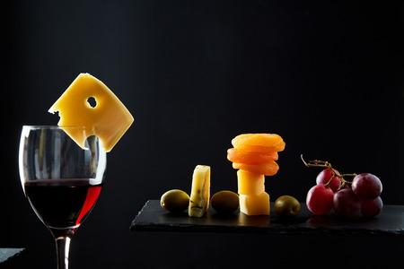 Glass of tasty red wine next assorted traditional appetizers on black background