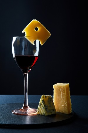 Glass of delicious red wine garnished with piece of cheese and rosemary on black background