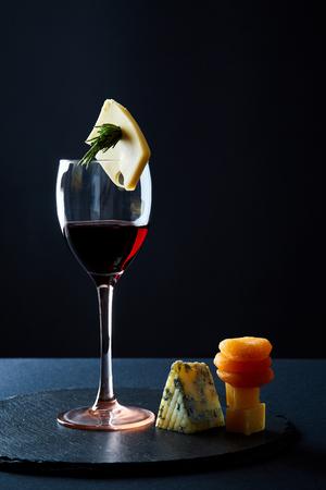 Copa de delicioso vino tinto aderezado con un trozo de queso y romero sobre fondo negro Foto de archivo