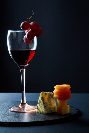 Glass of delicious red wine garnished with bunch of grapes on black background