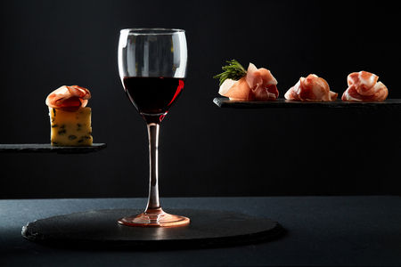 Composition of red wine in glass and pieces of meat snack on black background