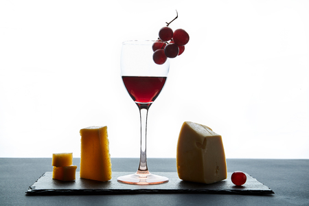 Glass of red wine garnished with grape and different kinds of cheese